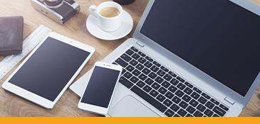 Een laptop, mobiel en tablet op een tafel.