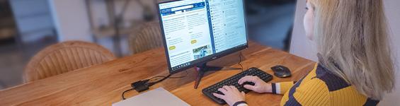 Vrouw werkend aan keukentafel op laptop met extra monitor.